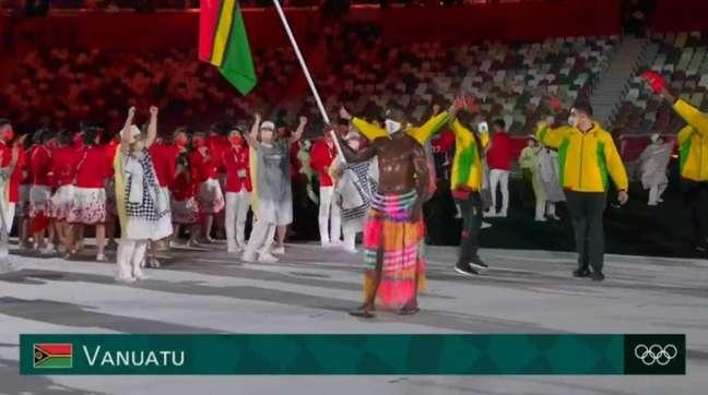 Remador Riilio Rii foi o porta-bandeira para a delegação de Vanuatu e ganhou fama na internet por 'rivalizar' com o porta-bandeira de Tonga que 'lançou a moda' dos 'besuntados' (Reprodução / SporTV)