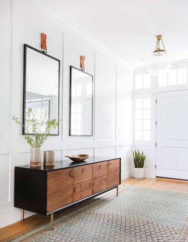 41. Hall branco decorado com espelho grande e buffet de madeira – Foto: Apartment Therapy