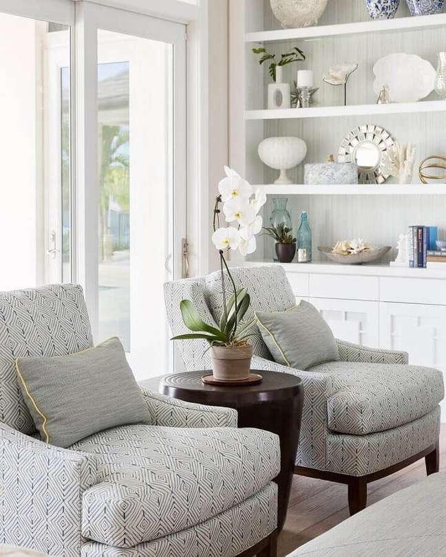 17. Objetos de decoração para estante de sala clean decorada com poltronas confortáveis – Foto: Foto Home Bunch