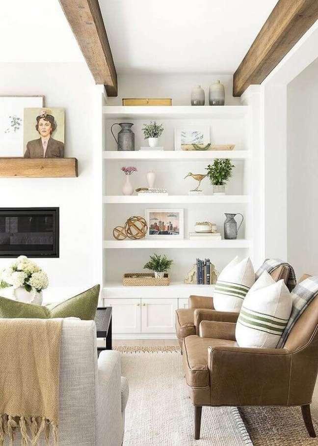 1. Objetos de decoração para estante de sala branca planejada com poltronas de couro marrom – Foto: Sout and Nimble