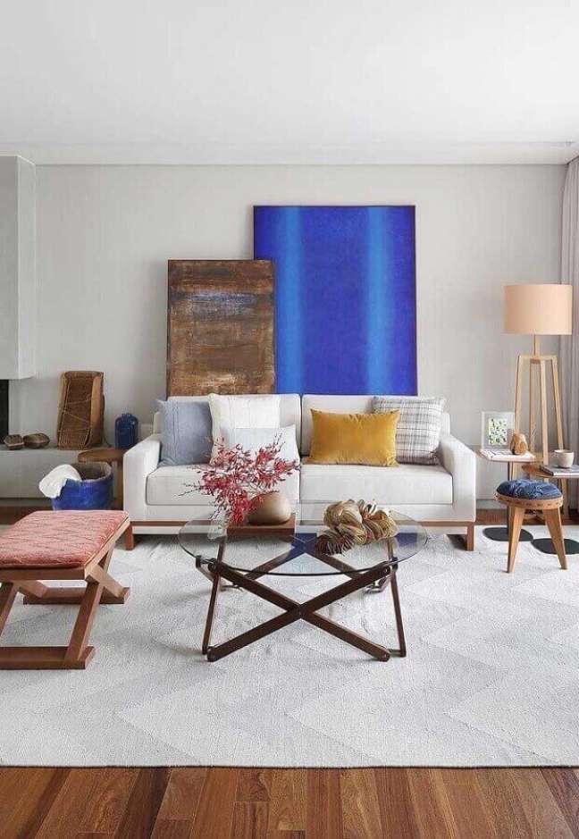60. Objetos para decoração de sala com quadros grandes e mesa de centro de vidro – Foto: Pinosy