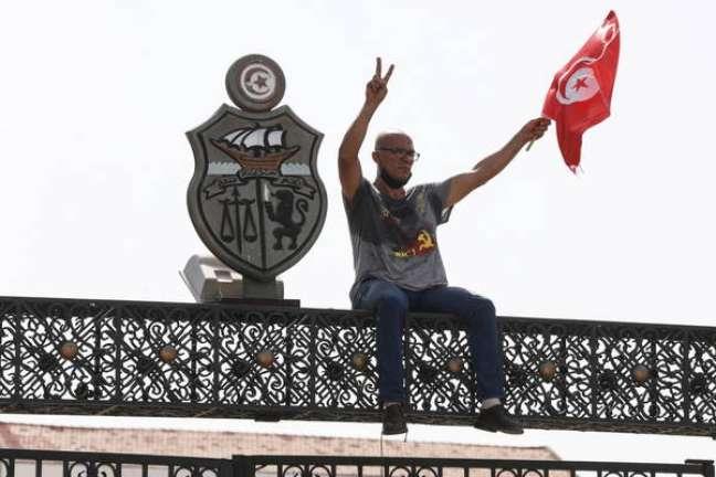 Manifestante comemora destituição de premiê no topo do Parlamento, em Túnis