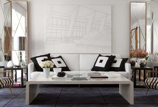 57. Objetos para decoração de sala com espelho grande e almofadas para sofá branco – Foto: Beto e Norea