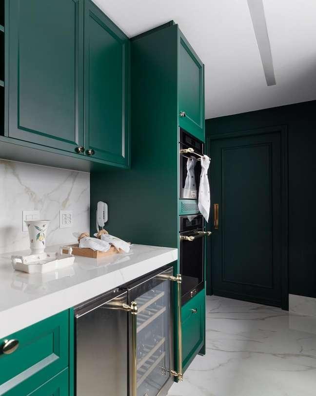 11. A solução criada para otimizar o espaço da cozinha foi embutir os eletrodomésticos na marcenaria. Foto: Fellipe Lima