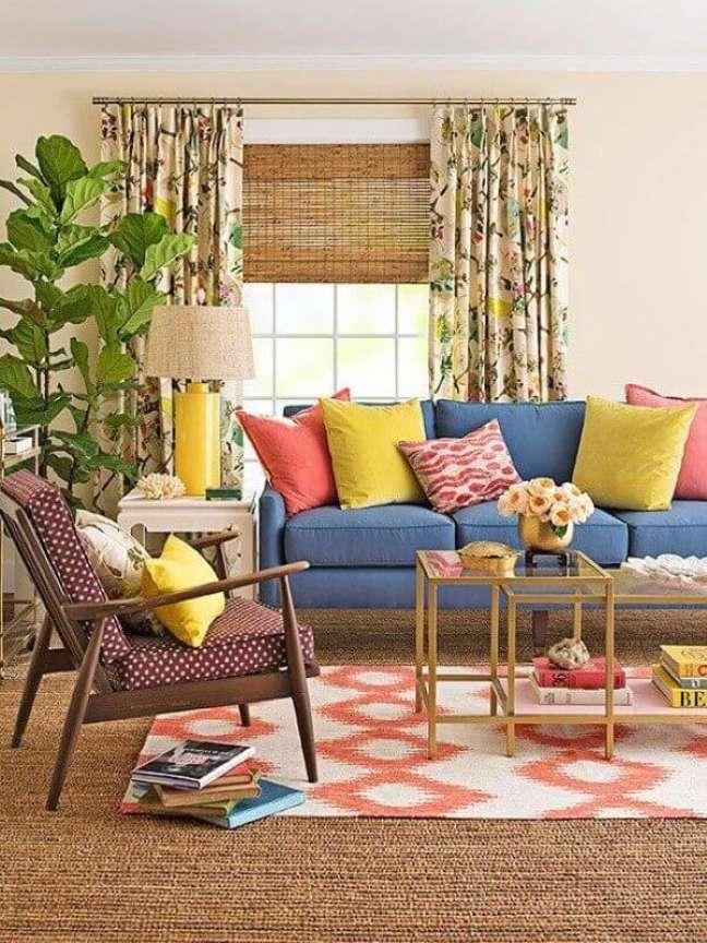 27. Objetos de decoração para sala de estar com almofadas coloridas e poltrona de madeira – Foto: Better Homes and Gardens