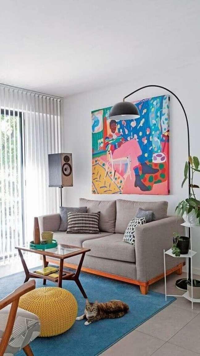 49. Objetos de decoração para sala pequena com sofá cinza e quadro grande colorido – Foto: Pinterest