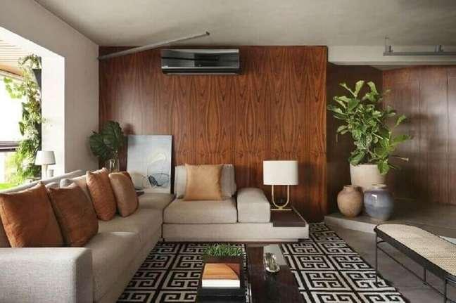 30. Objetos de decoração para sala de estar com tapete geométrico e parede de madeira – Foto: Quattrino Arquitetura