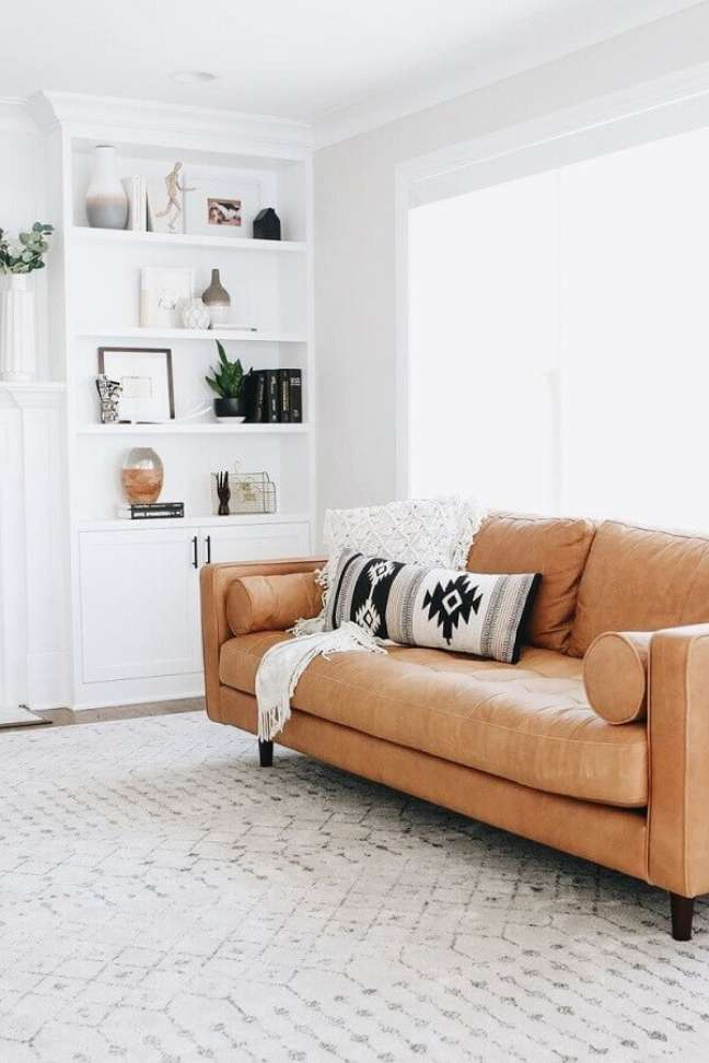 16. Objetos de decoração para estante de sala branca decorada com sofá de couro caramelo – Foto: Pinterest