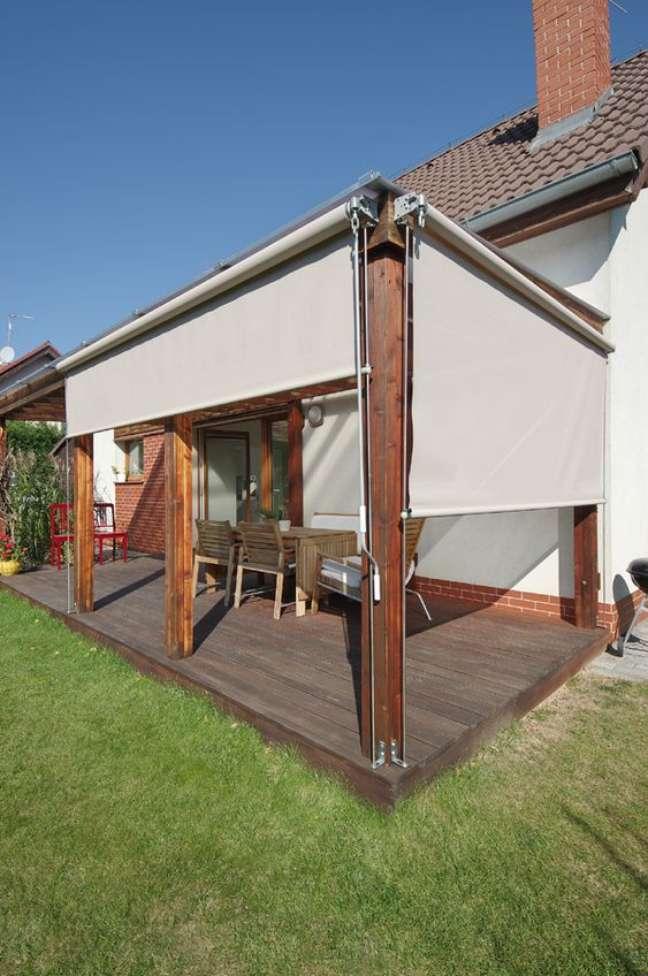 43. Toldo vertical para varanda com móveis de madeira para proteger o espaço da chuva e sol – Foto Ebarch