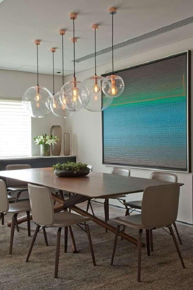 41. Luminária de vidro para sala de jantar decorada com quadro grande – Foto: Casa de Valentina