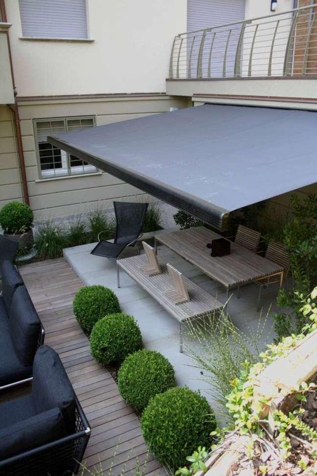 33. Toldo para varanda preto com móveis de madeira e plantas na decoração – Foto Archilovers