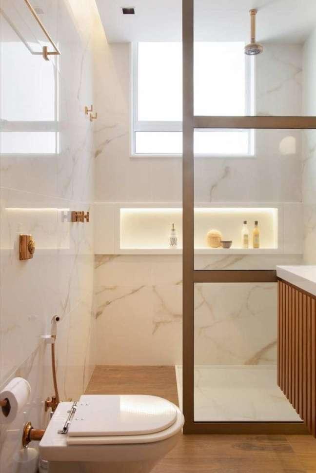 66. Nicho de embutir para banheiro com azulejo marmorizado e piso amadeirado – Foto Casa de Valentina