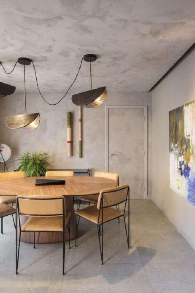 6. Luminária para sala de jantar moderna decorada com parede de cimento queimado e mesa redonda de madeira – Foto: ArchDaily