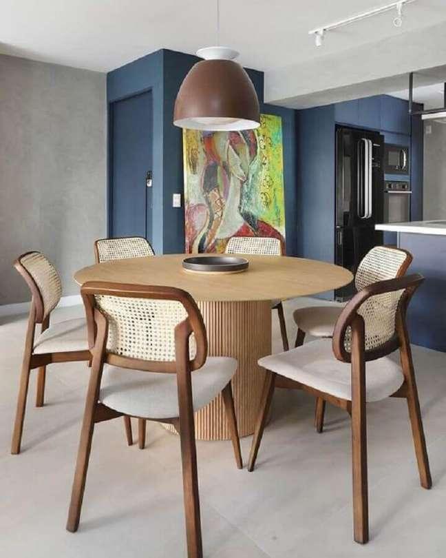 34. Luminária de teto para sala de jantar decorada com mesa redonda e cadeira de palhinha – Foto: Pinterest