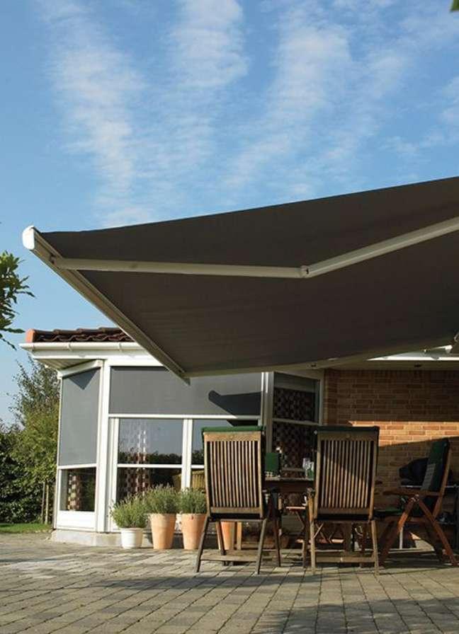 29. Toldo para varanda moderna com mesa e cadeiras de madeira – Foto Botex
