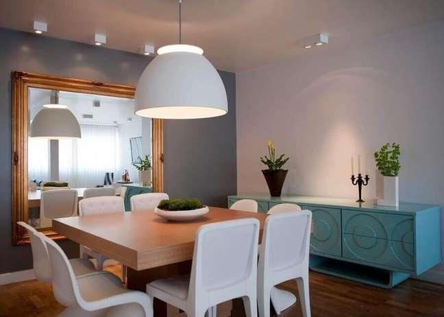 46. Luminária para sala de jantar cinza decorada com espelho grande e buffet azul – Foto: Ih Designers