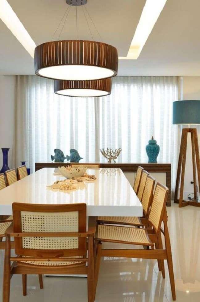62. O acabamento em madeira da luminária para sala de jantar se harmonizou com os móveis do ambiente. – Foto: Homify