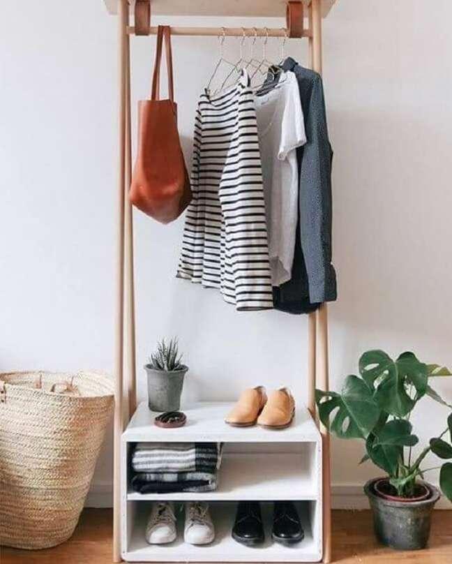 56. Organize sapatos e roupas de cama na arara de roupas de madeira. Fonte: Decostore