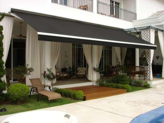 1. Toldo para varanda articulado na cor preta com parede externa creme – Foto Criativa Coberturas