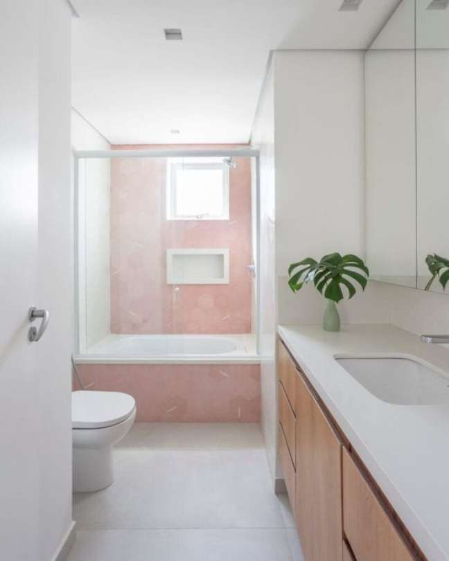 29. Nicho de embutir para banheiro rosa com móveis de madeira – Foto Pinterest