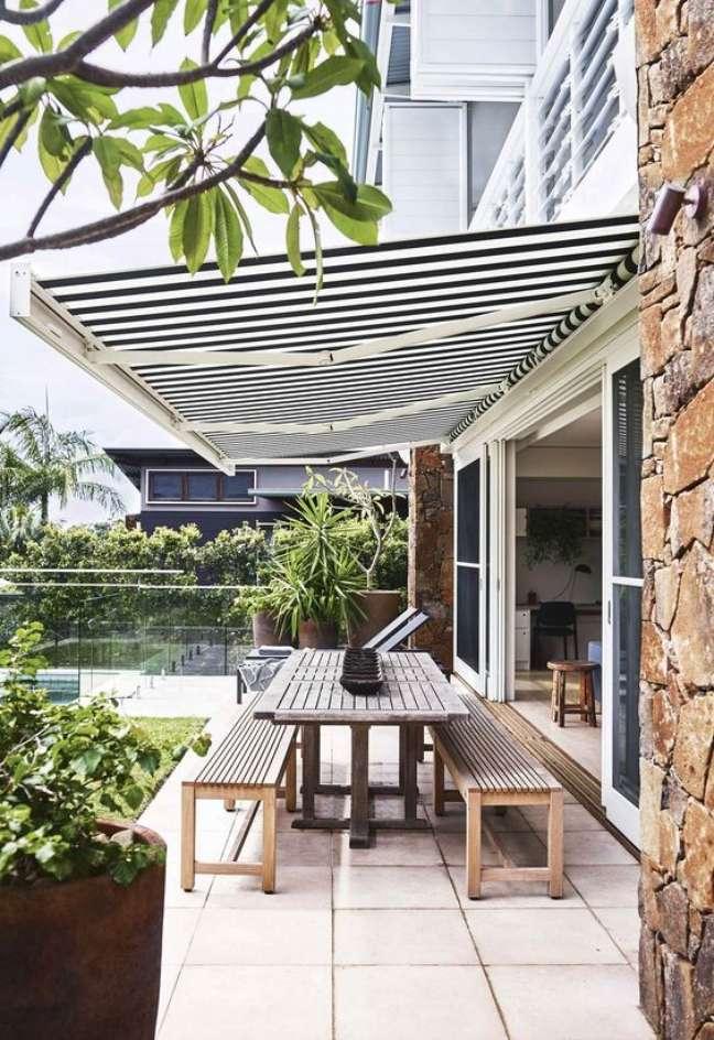 12. Toldo para varanda com mesa de madeira na área externa – Foto Homesto love
