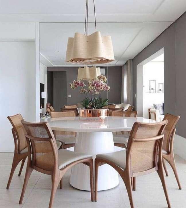 54. Luminária para sala de jantar moderna decorada com mesa redonda e parede espelhada – Foto: Pinterest
