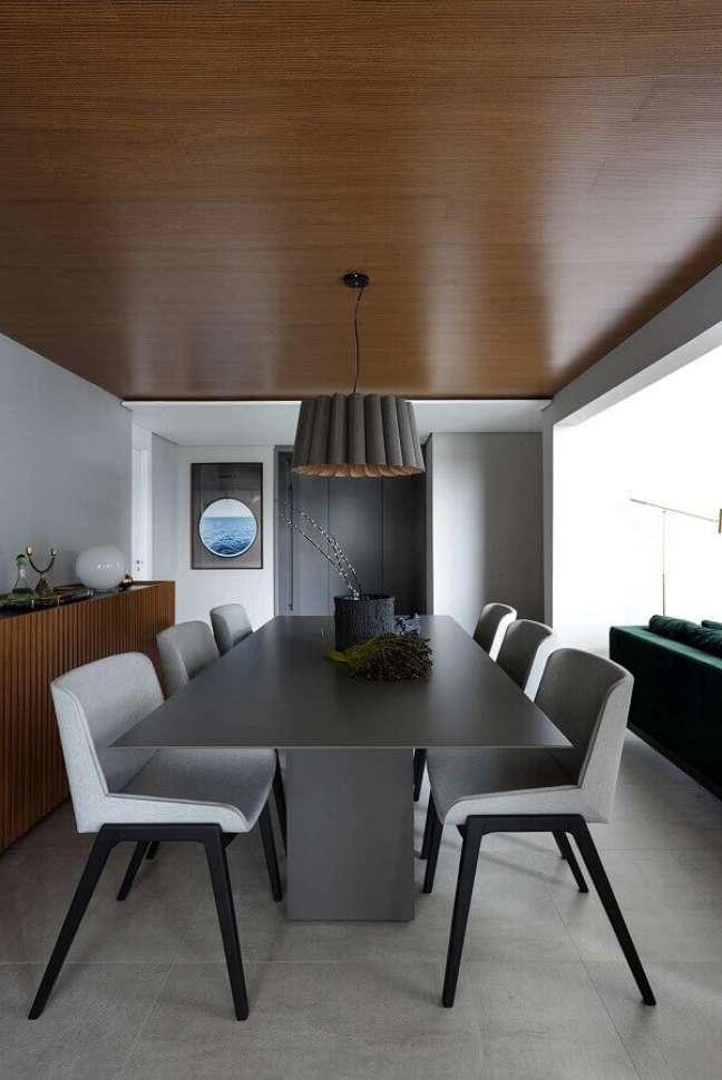 56. Luminária para sala de jantar moderna decorada em tons de cinza com buffet de madeira – Foto: Casa de Valentina