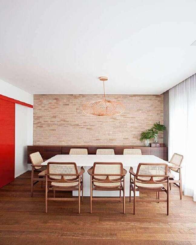 36. Luminária de teto para sala de jantar decorada com parede tijolinho e buffet de madeira – Foto: Korman Arquitetos