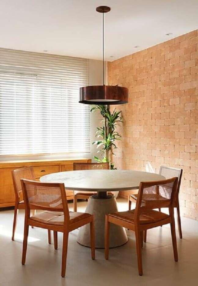 63. Luminária redonda para sala de jantar decorada com parede tijolinho – Foto: Sadala Gomide