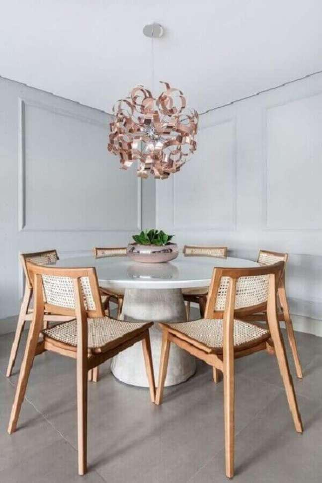 53. Luminária para sala de jantar moderna decorada com mesa redonda e cadeira de madeira – Foto: Pinterest