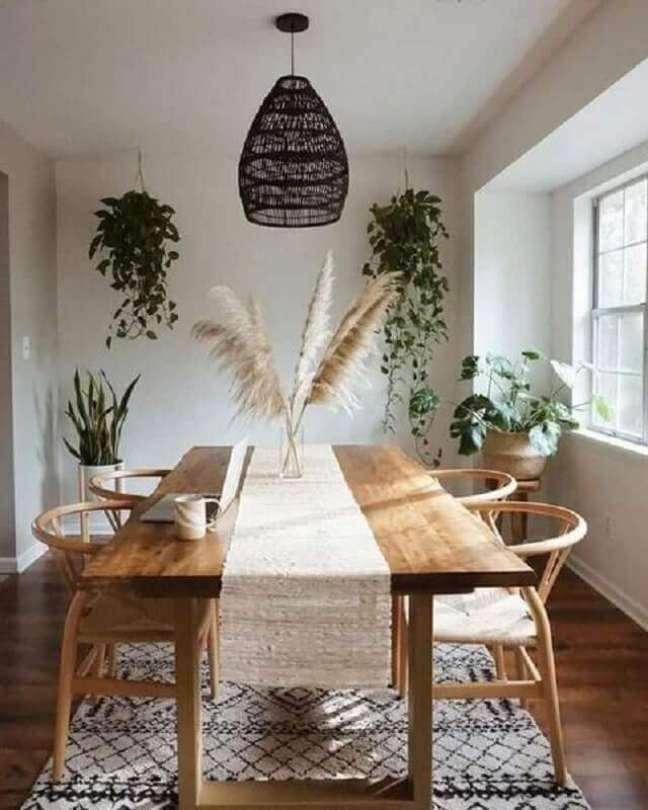 60. Luminária preta para sala de jantar decorada com vasos de plantas e mesa de madeira – Foto: Pinterest