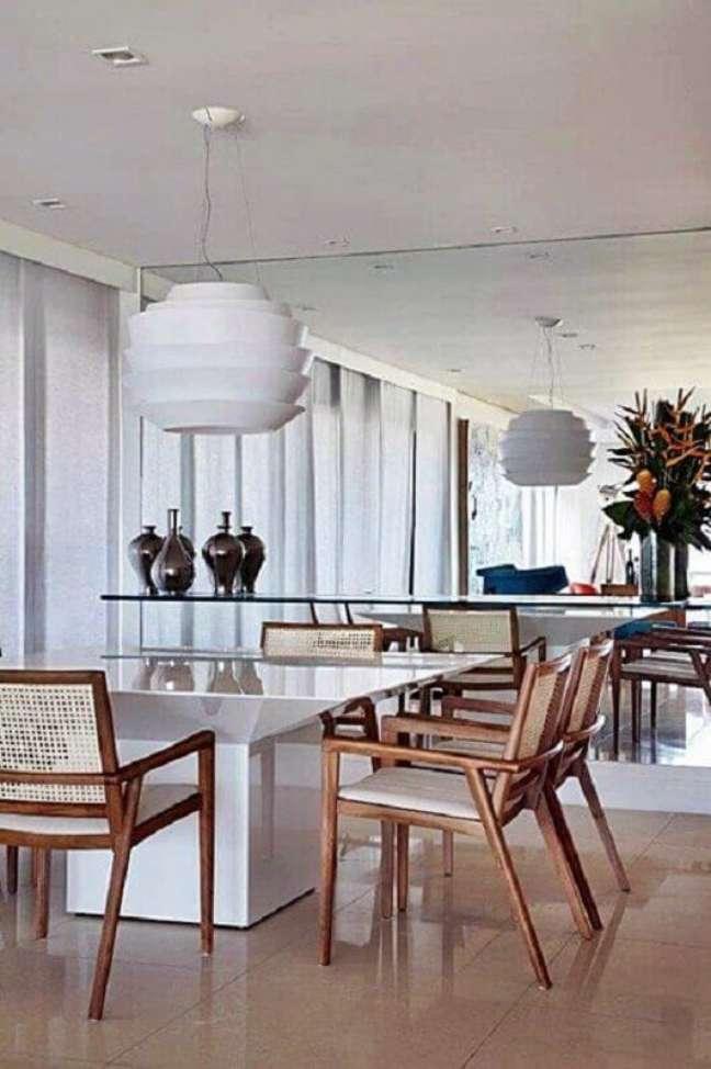 43. Luminária para sala de jantar branca decorada com parede espelhada e cadeiras de madeira – Foto: Simples Decoração