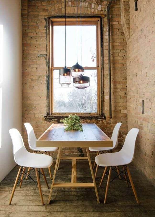57. Luminária para sala de jantar pequena e rústica decorada com cadeira eames branca e parede tijolinho – Foto: South Central