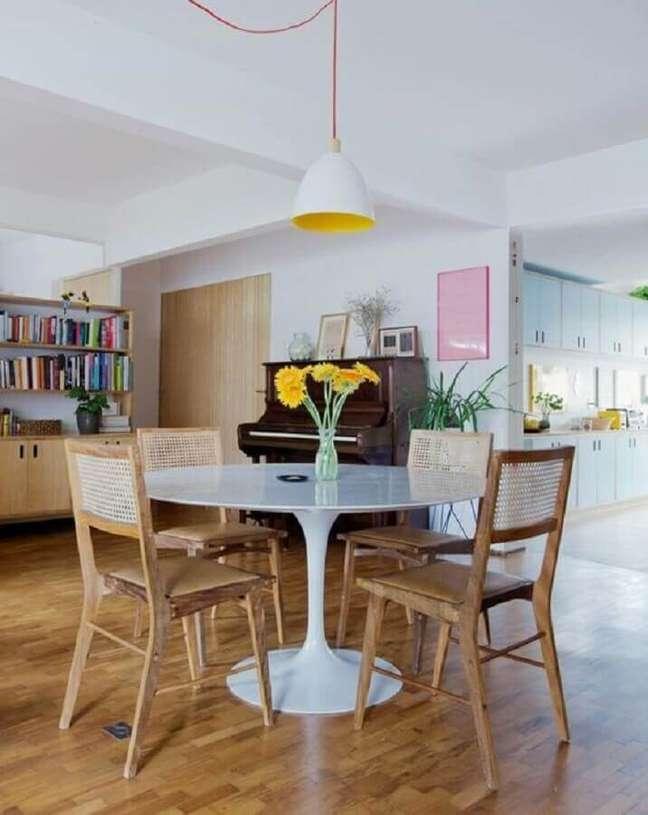 67. Luminária simples para sala de jantar decorada com mesa redonda e cadeira de madeira com encosto de palha – Foto: Histórias de Casa
