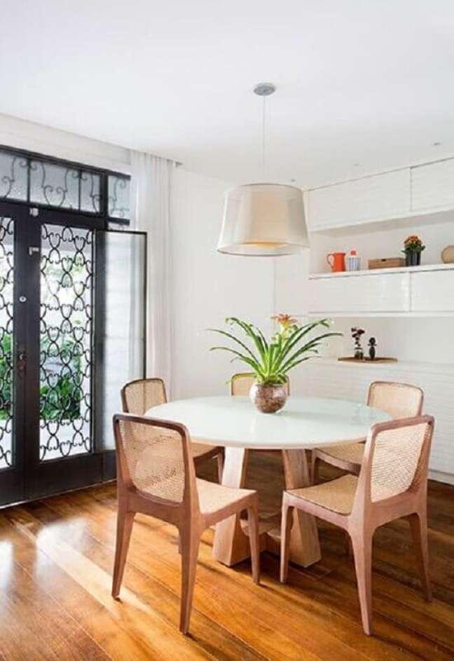 58. Luminária para sala de jantar simples decorada com cadeiras de madeira para mesa branca redonda – Foto: Sadala Gomide