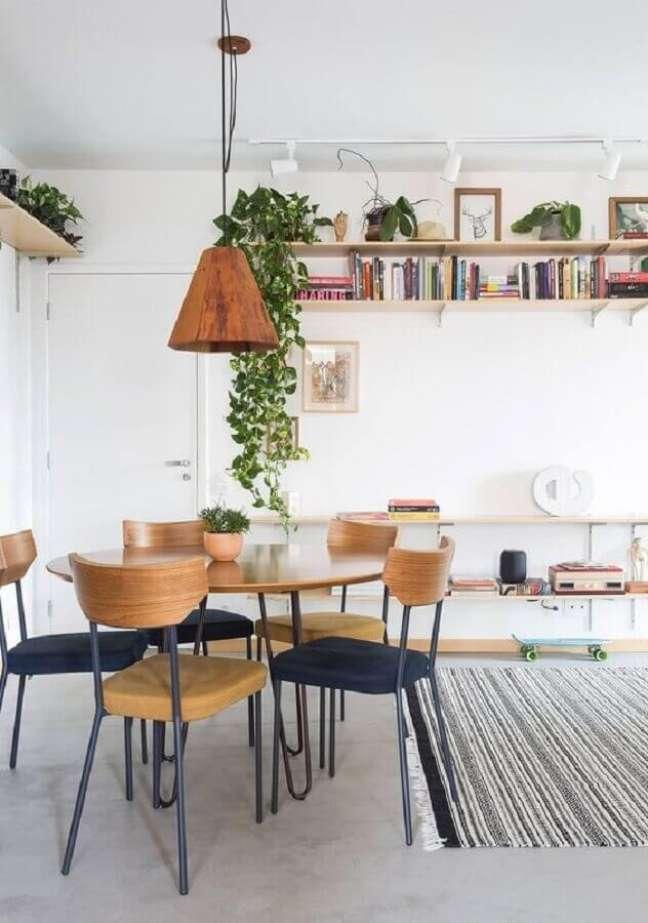 59. Luminária para sala de jantar simples decorada com vasos de plantas e prateleiras para livros – Foto: Histórias de Casa