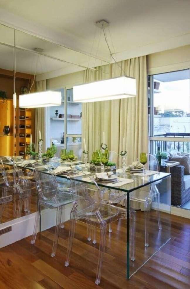 70. Luminárias para sala de jantar pequena decorada com parede espelhada e mesa de vidro – Foto: Jeito de Casa