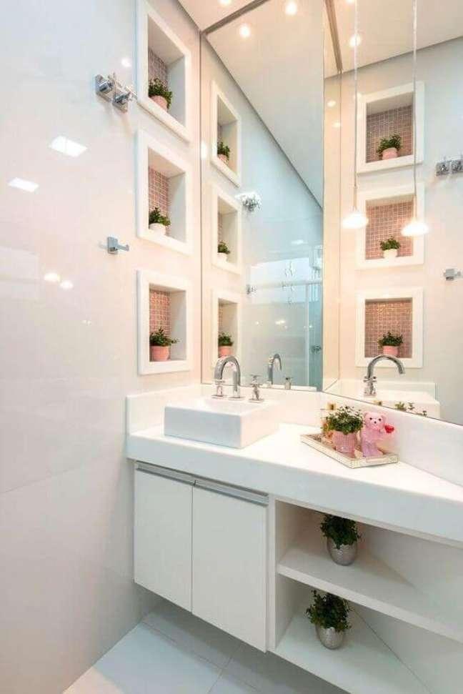 18. Nicho de embutir para banheiro de porcelanato branco decorado com pastilhas cor de rosa e vasos de plantas – Foto Revista VD