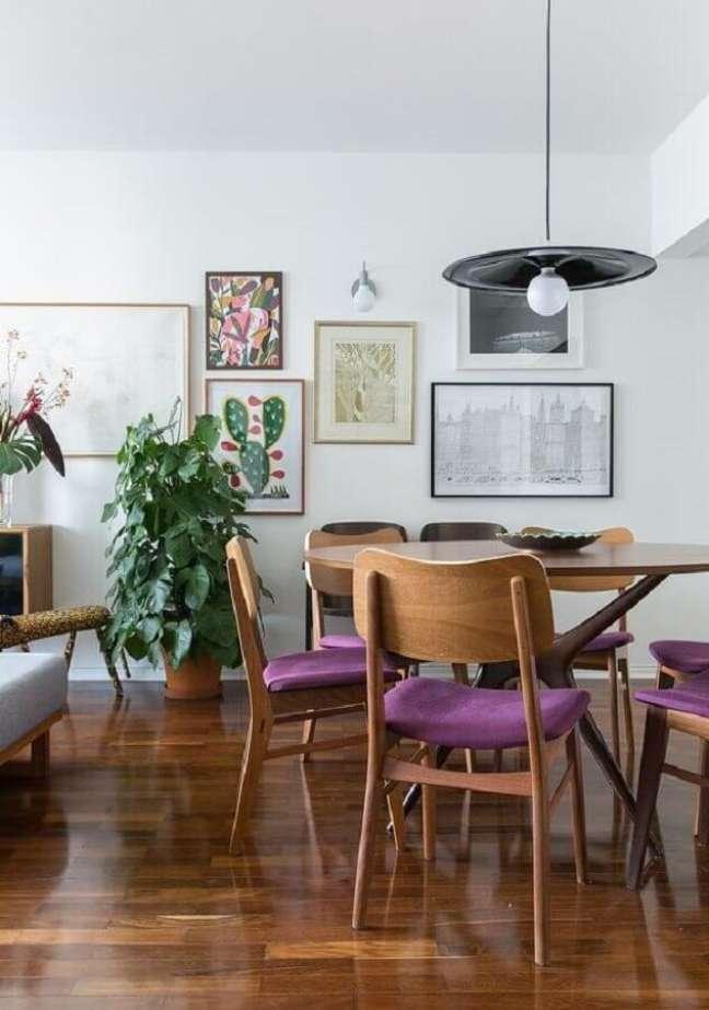 69. Luminária simples para sala de jantar decorada com quadros de parede e cadeira estofada roxa – Foto: Histórias de Casa