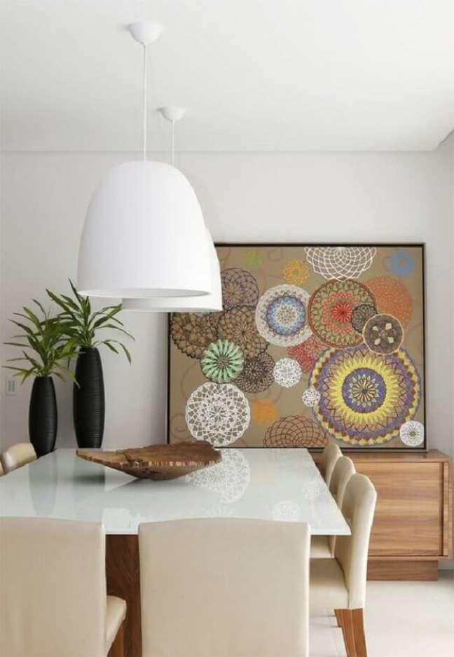 44. Luminária para sala de jantar branca decorada com quadro grande apoiado em buffet de madeira – Foto: Casa de Valentina