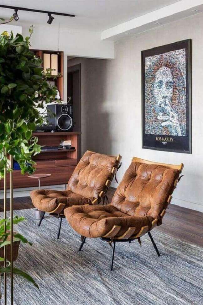 92. Sala moderna decorada com quadros de famosos e poltronas em couro – Foto Histórias de Casa