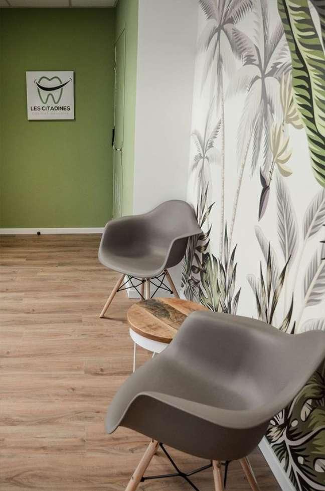 30. Consultório dentário com sala de espera decorada com papel de parede de plantas e cadeira cinza – Foto Decogite