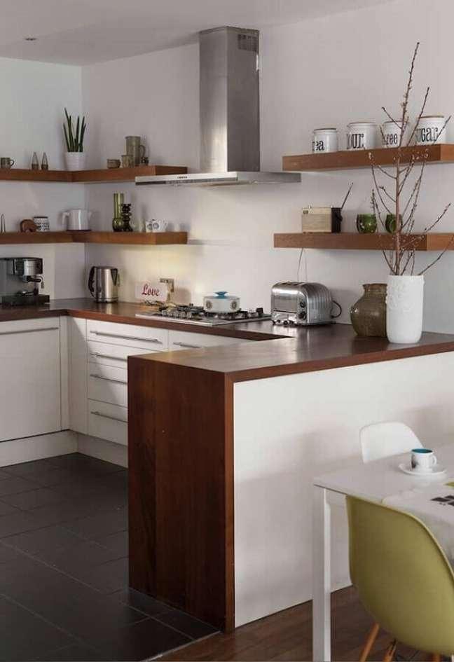 55. Estilo de cozinha americana em U decorada com prateleiras e bancada de madeira – Foto: Pinterest