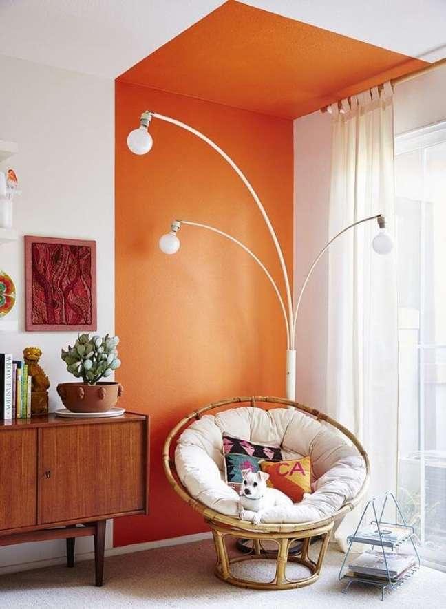 3. Parede de sala decorada com pintura setorizada laranja perto do rack de madeira e poltrona de ratan – Foto Pinterest