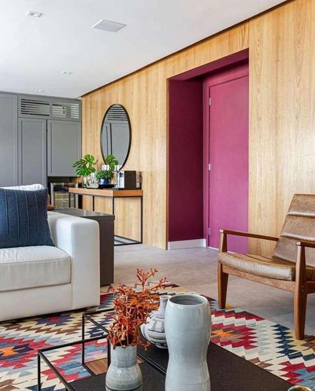 60. Parede de sala decorada com revestimento de madeira e porta de madeira pintada de marsala – Foto Assim eu Gosto