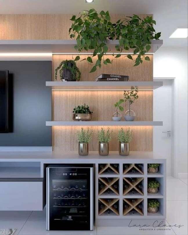 80. Sala de TV com parede decorada com prateleiras e mini bar – Foto Pinterest