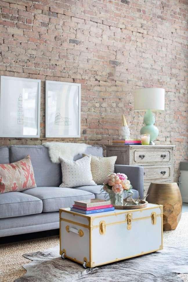 94. Sala vintage decorada com papel de parede de tijolinho e bau de madeira azul e dourado no centro do ambiente – Foto Fashionismo