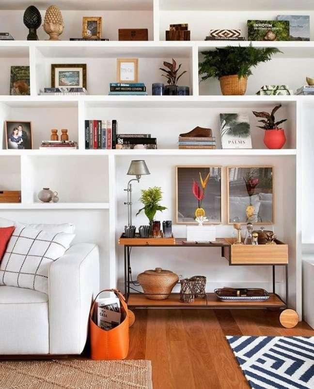 125. Sala de estar com uma estante planejada e enfeites variados – Foto Assim Eu Gosto