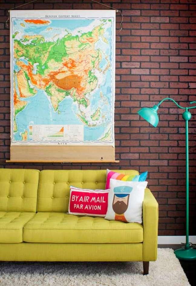45. Parede de sala decorada com papel de parede de tijolinho e quadro de mapas coloridas com almofadas divertidas no sofá amarelo — Foto Pinterest