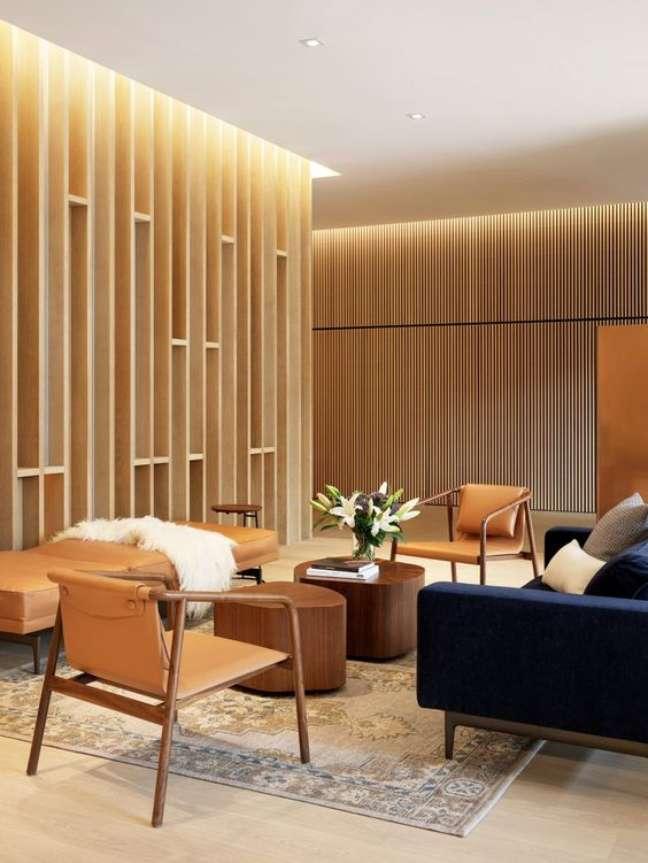 59. Sala de espera com sofá azul marinho cadeiras de madeira e chaise de couro – Foto Dezeen